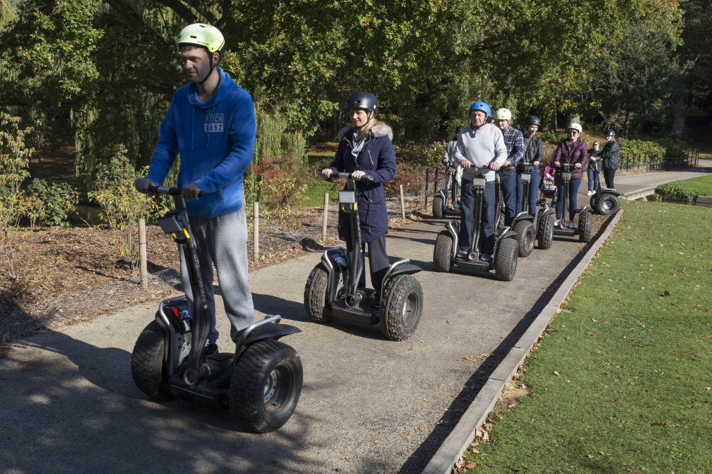 People on Segways line up to enter a castle tour.