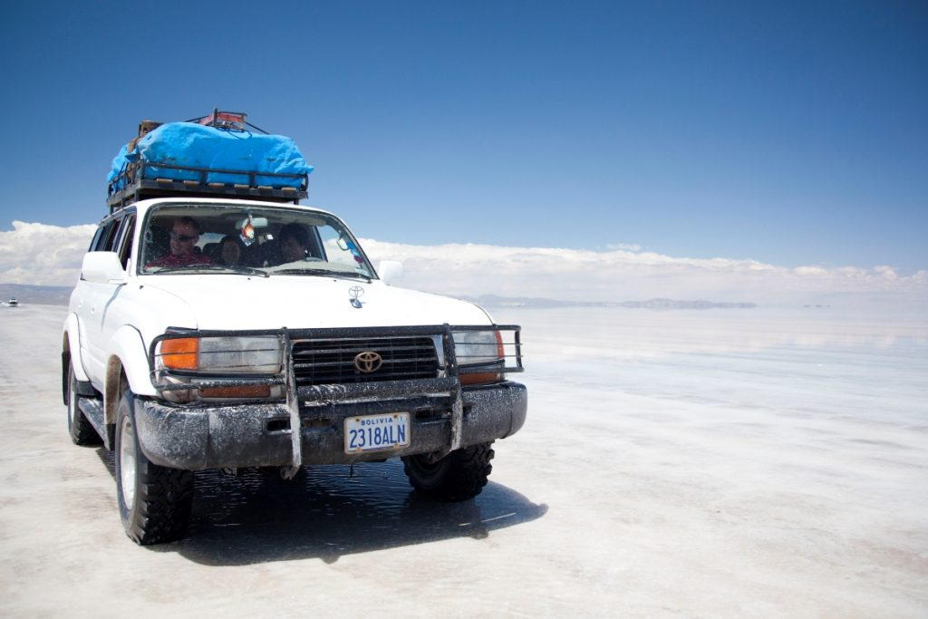 A white Toyota Landcruiser crosses Salt Flats in Bolivia