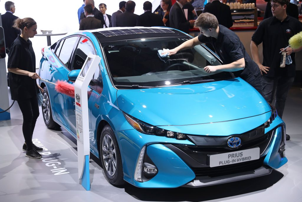 Workers prepare a Toyota Prius plug-in hybrid at the 2017 Frankfurt Auto Show on September 12, 2017