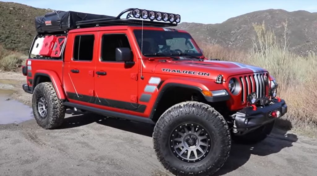 A red Jeep Gladiator parked on a dirt road
