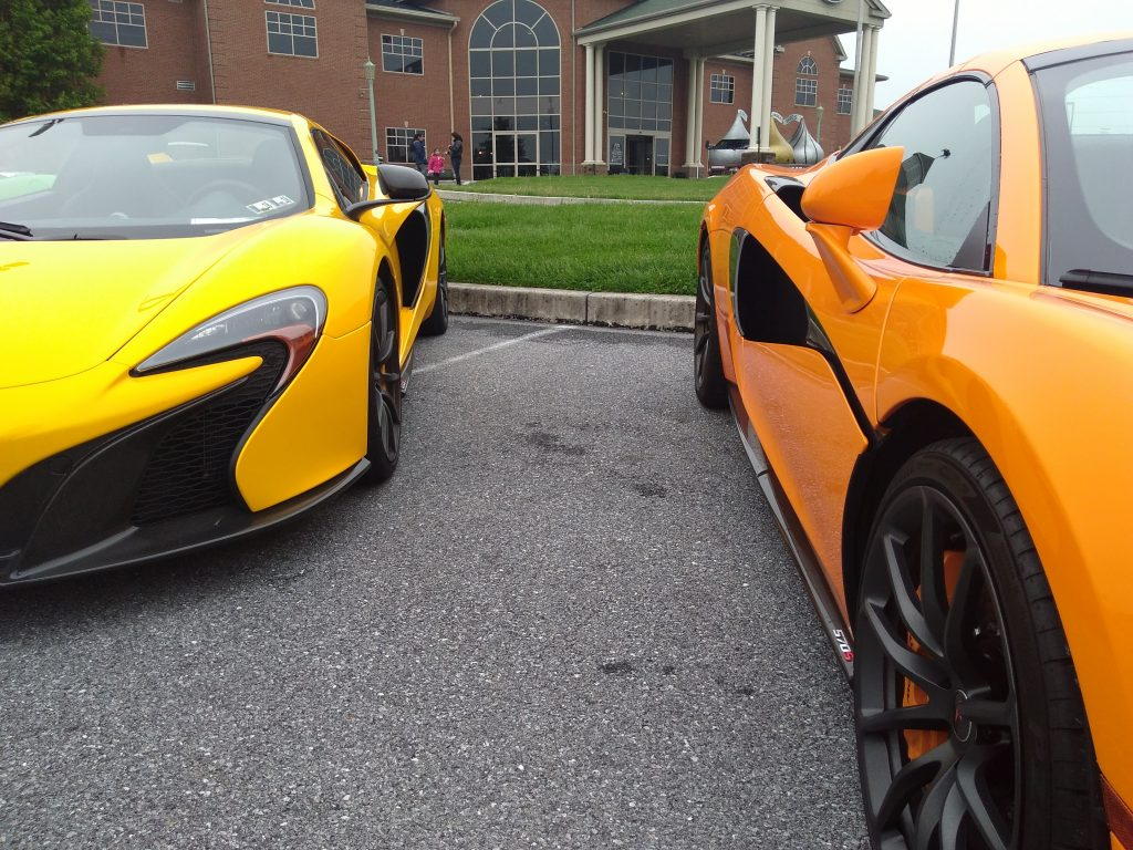 A yellow and orange McLaren sit side-by-side in a parking lot