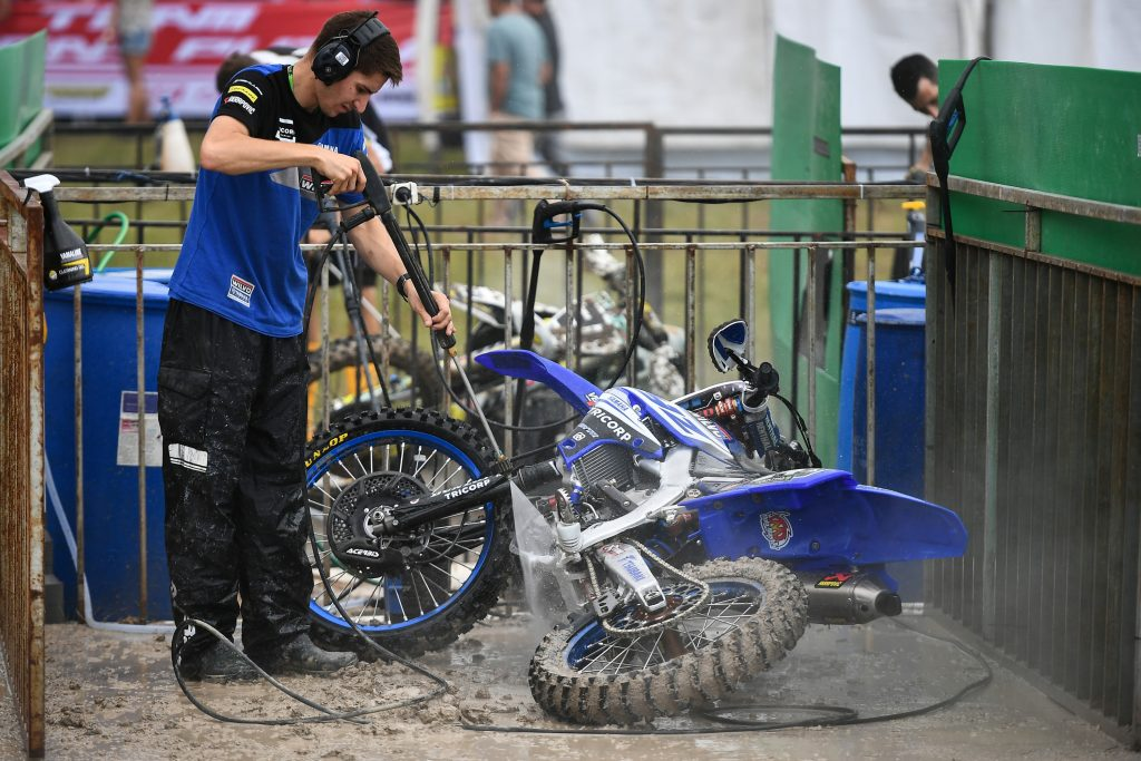 Monster Energy Yamaha Factory MXGP Team crew washes a motorcycle using a pressure washer