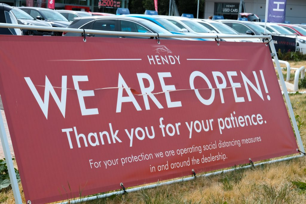 A, We Are Open, sign is in front of a car dealership. Re-opened after taking COVID-19 precautions.
