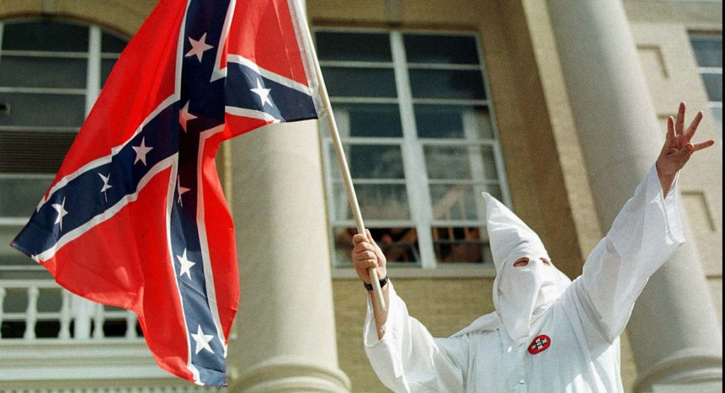 A member of the American Knights of the Ku Klux Klan waves the confederate flag during a klan rally in Indiana