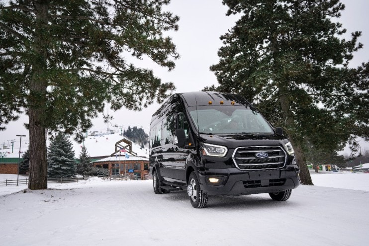 A black Ford transit passenger van in the snow