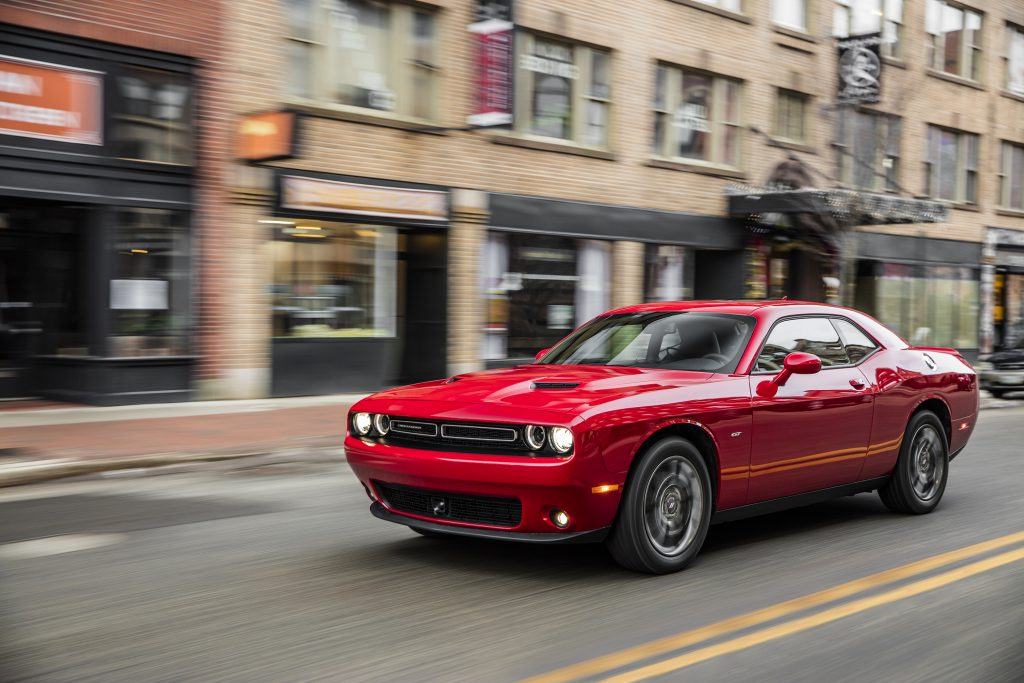 A red Dodge challenger driving on a city street