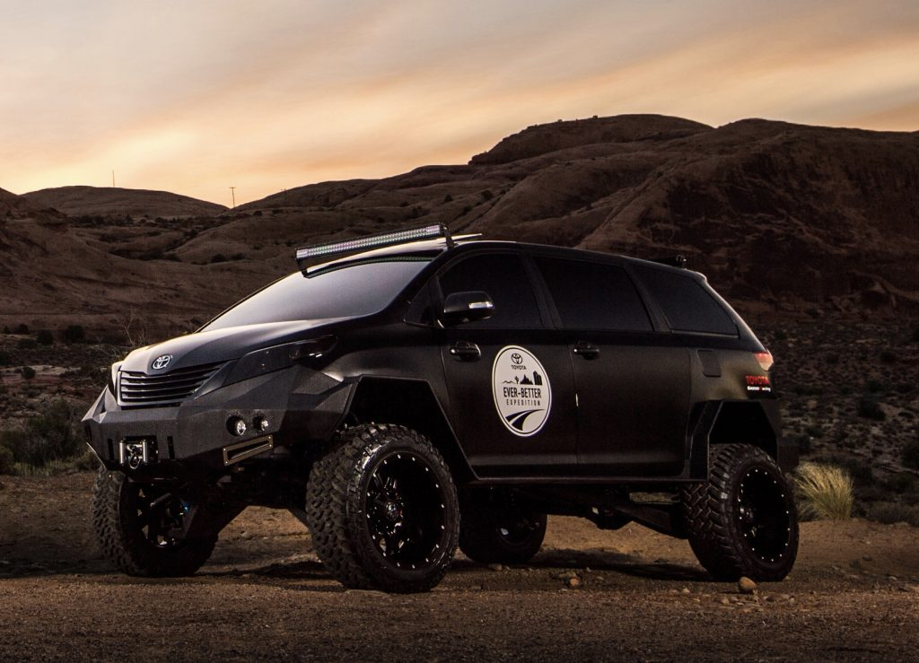 The black on black Toyota UUV overland vehicle with massive tires in a desert scene