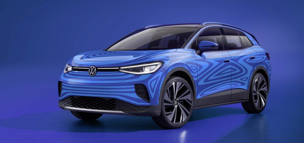 A blue Volkwagen electric SUV sits on display before a blue background.