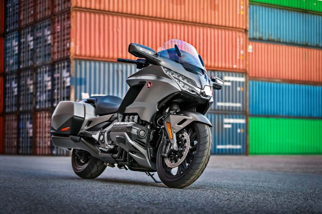 a parked Gold Wing Tour in a shipping yard with storage containers in the background