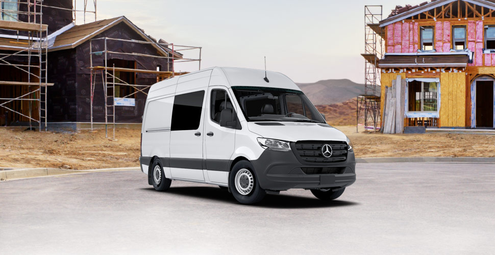 A white sprinter full-size cargo van on a construction site