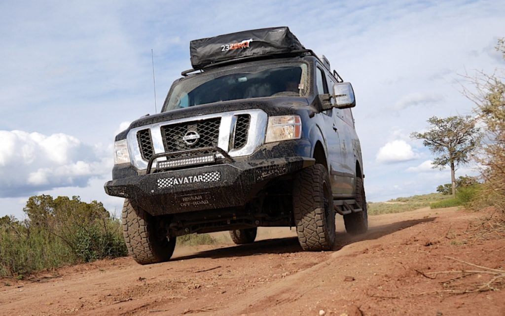 A black, lifted, 4x4, full-size van that has been converted for overlanding sits on a dirt road