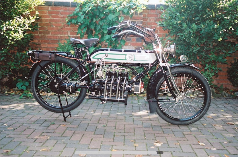 A silver-tanked 1913 FN Four in front of a garden wall
