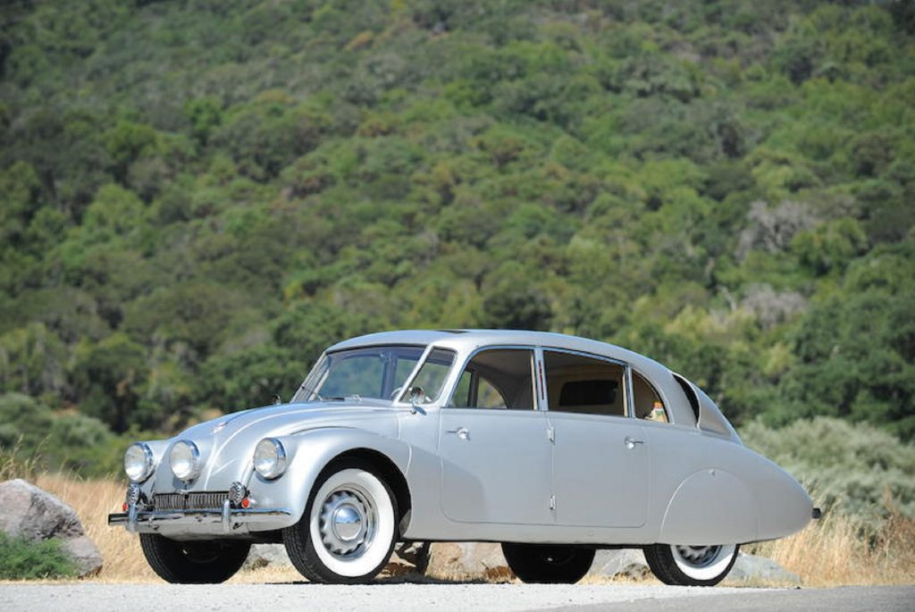 A silver 1941 Tatra T87 in front of a grassy hill