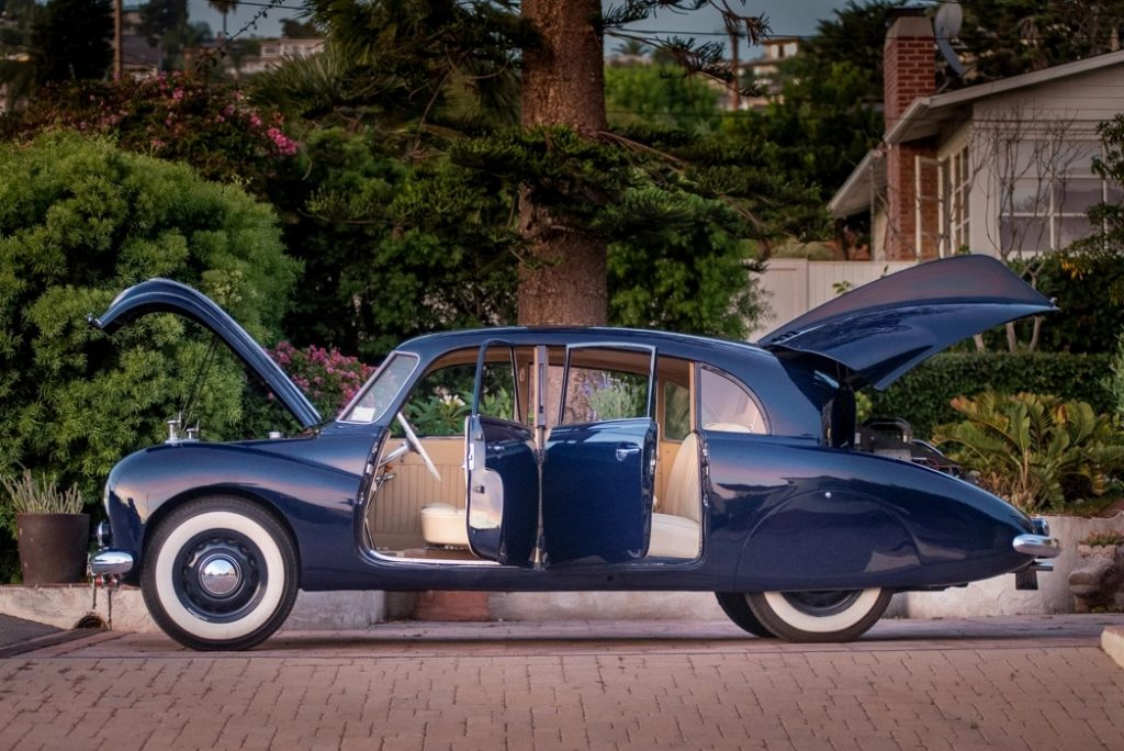A side-view of a dark-blue 1950 Tatra T87, with its doors, front trunk, and rear engline-lid open