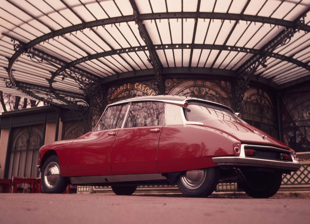Rear low-angle view of a red 1960 Citroen DS underneath a metal-and-glass dome