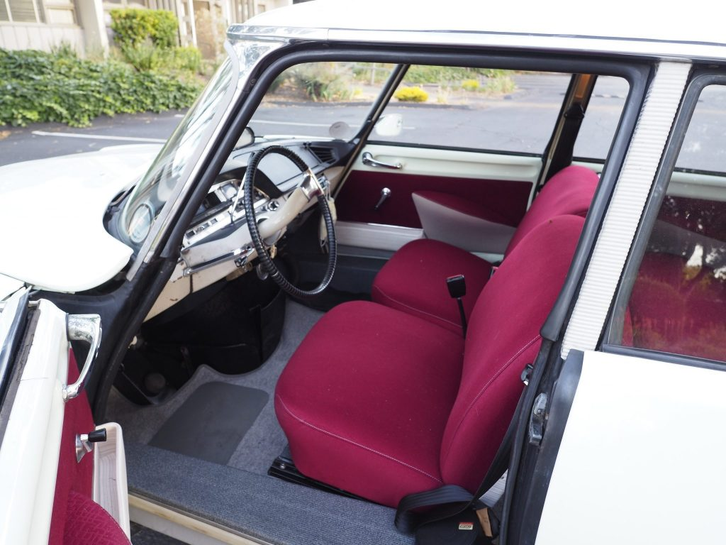 The interior of a white 1964 Citroen DS19, showing red seats and the push-button brake pedal