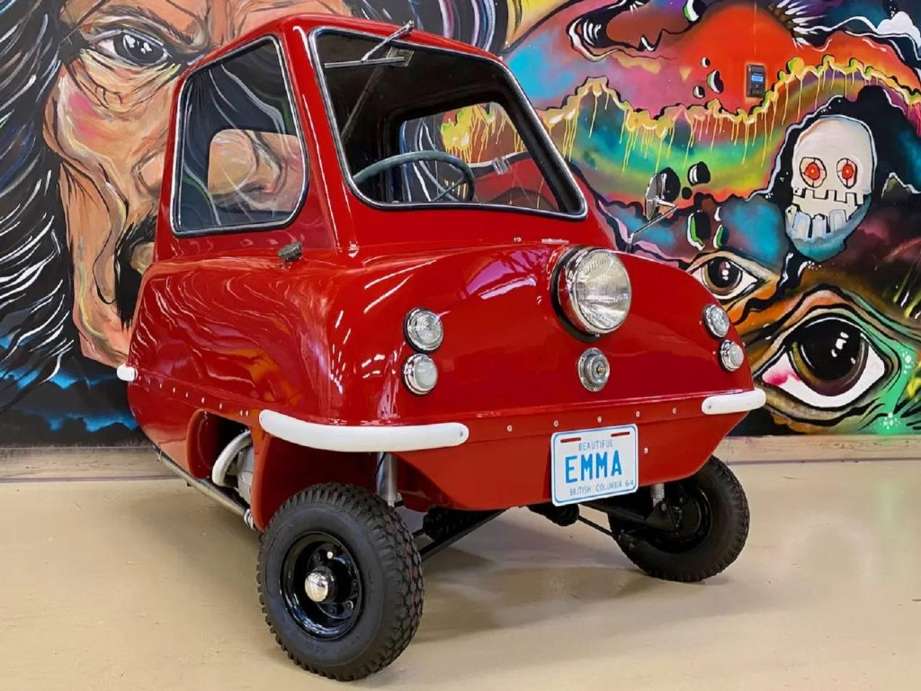 Red 1964 Peel P50 in front of a painted mural