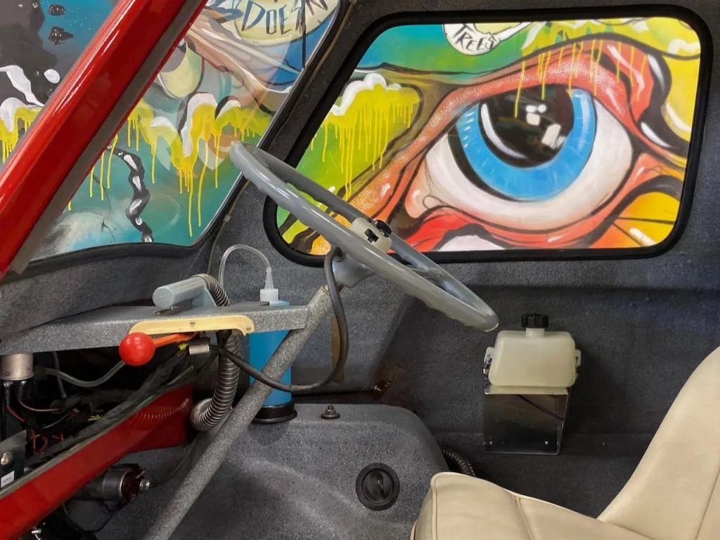 Side-shot of a 1964 Peel P50's interior, showing the steering wheel and single seat