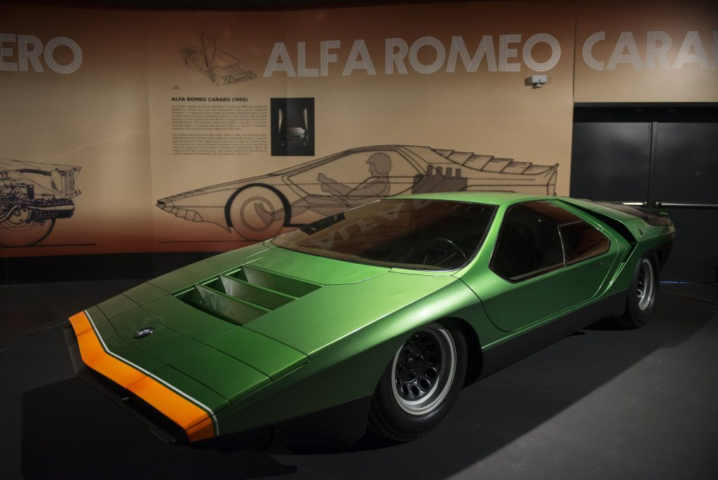 A green low slung sports car from Alfa Romeo sits in an exhibit.