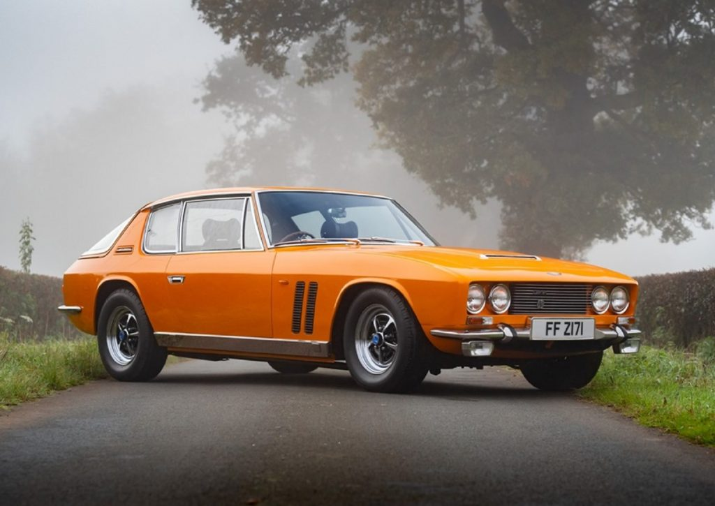 An orange 1969 Jensen Interceptor FF Mk I on a foggy countryside road