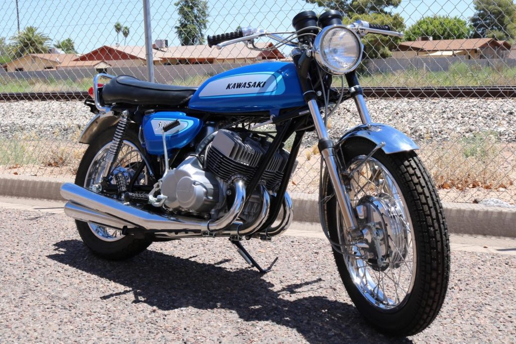 Blue 1971 Kawasaki H1 Mach III in front of a chain-link fence