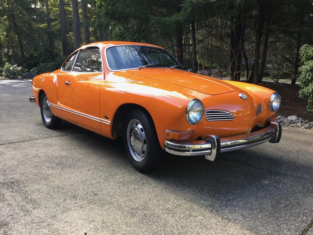 An orange 1972 Volkswagen Karmann Ghia coupe parked in a forest