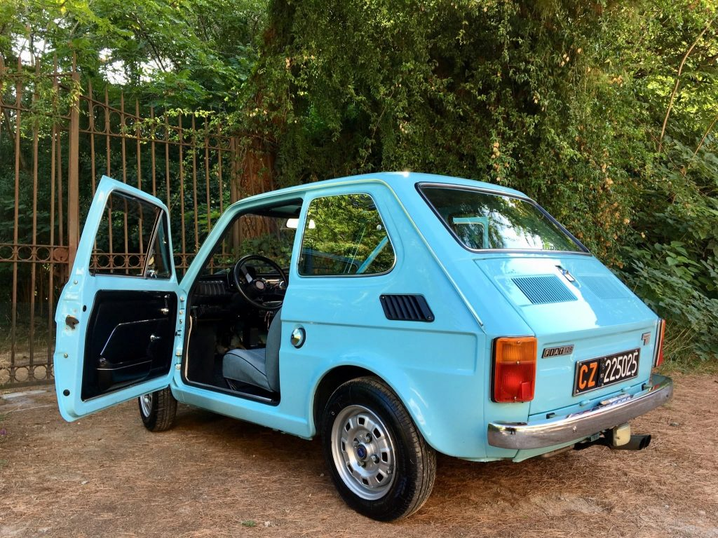 Rear view of a blue 1979 Fiat 126p, with its door open and showing some of the interior
