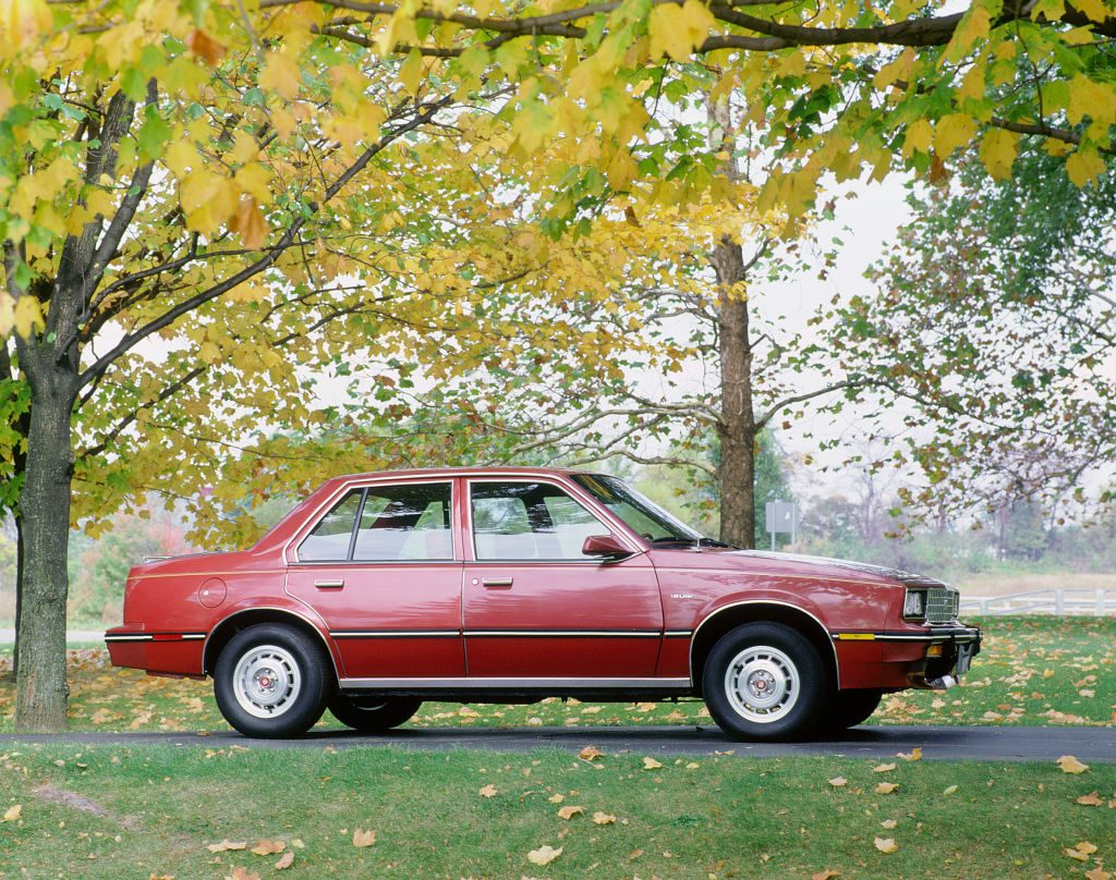 red Cadillac Cimarron on grass