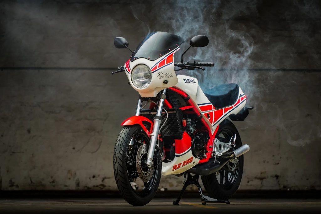 Red-and-white 1985 Yamaha RZ350 Kenny Roberts Edition with 2-stroke smoke wafting around it