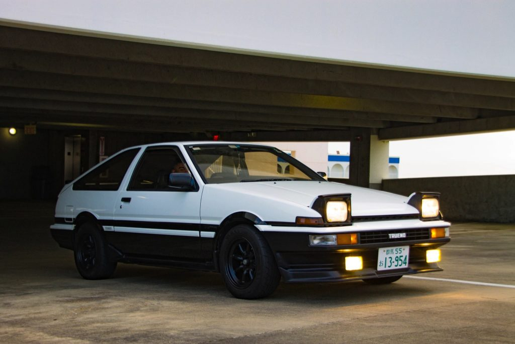 White 1986 Toyota AE86 Sprinter Truneo with headlights popped up, underneath a parking garage roof