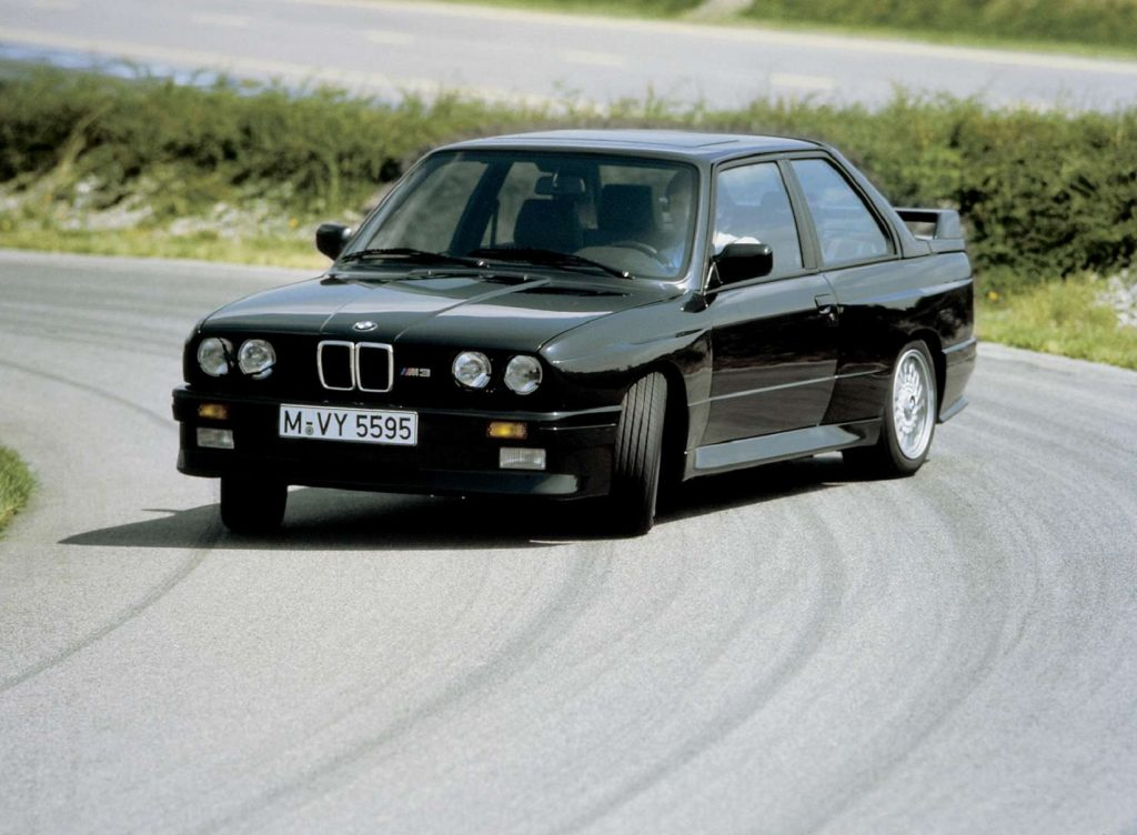A black 1987 BMW E30 M3 drifting around a racetrack corner