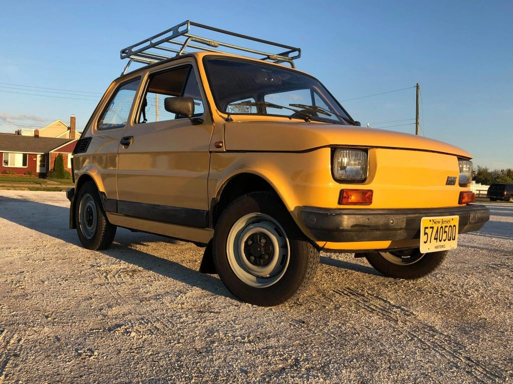 Yellow 1989 Fiat 126p hatchback with a roof rack on the beach
