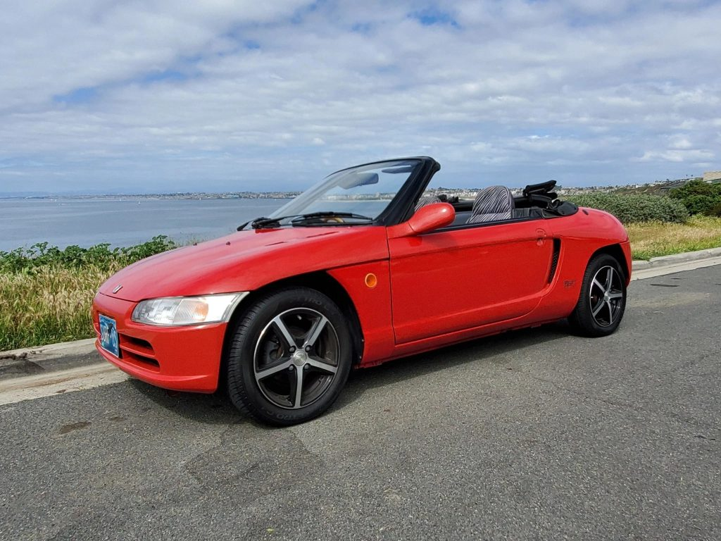 Red 1991 Honda Beat viewed from the side with the roof down