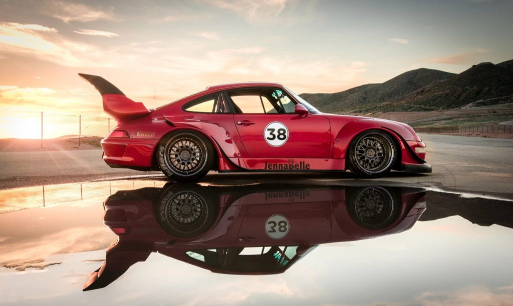 Side view of a red 1995 RWB Porsche 911 Carrera reflecting in a desert pool at sunset