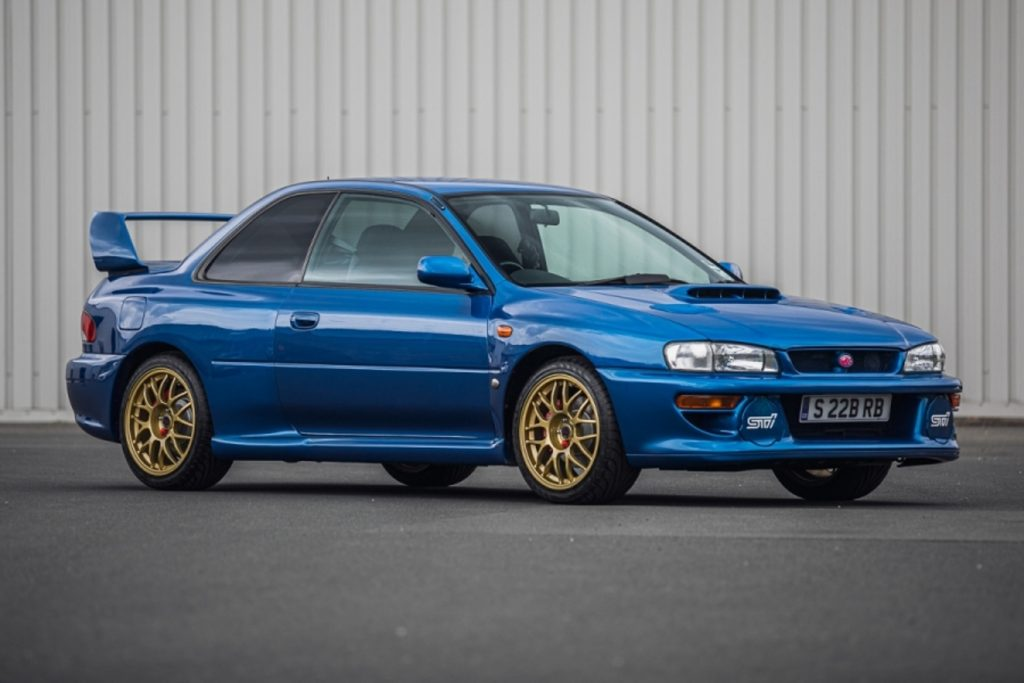 Blue 1998 Subaru Impreza 22B STi in front of a gray metal wall