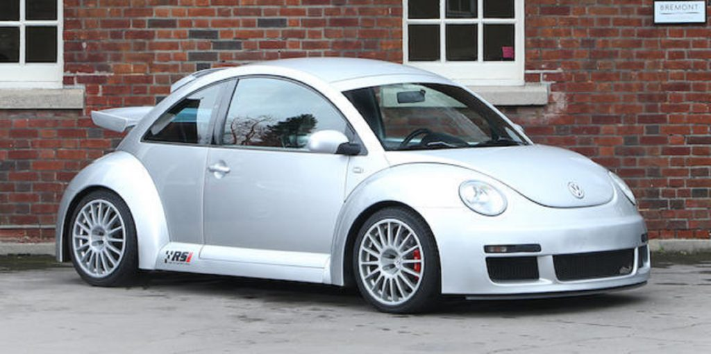 A silver 2001 Volkswagen Beetle RSI in front of a red-brick building