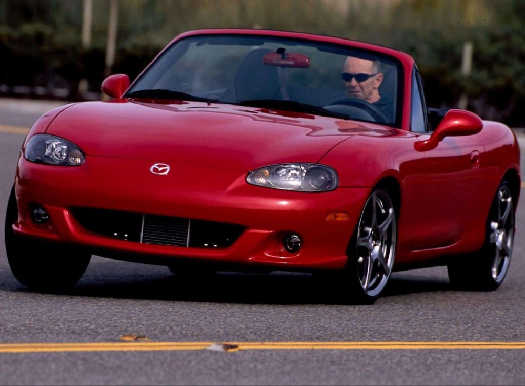 A red 2004 Mazdaspeed MX-5 Miata going around a corner
