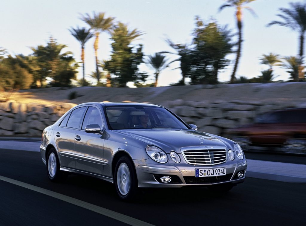 Silver 2006 Mercedes-Benz E-Class sedan driving down a road lined with palm trees