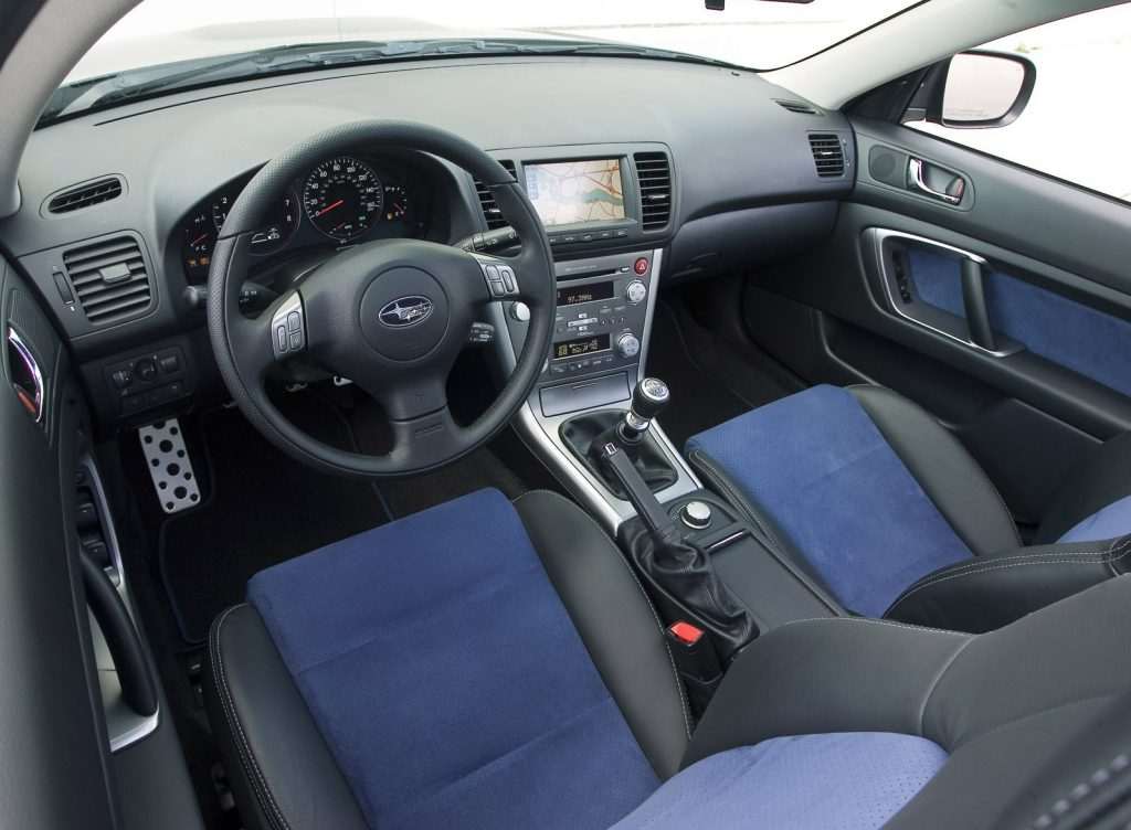 Interior shot of the 2007 Subaru Legacy 2.5GT Spec B, showing the 6-speed manual, blue-and-leather-trimmed seats, and navigation