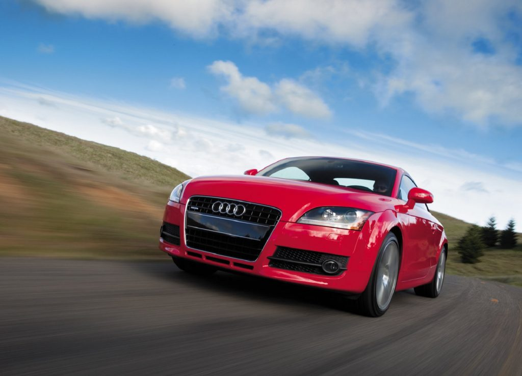 A low-angle shot of a red 2008 Audi TT Coupe driving down a road