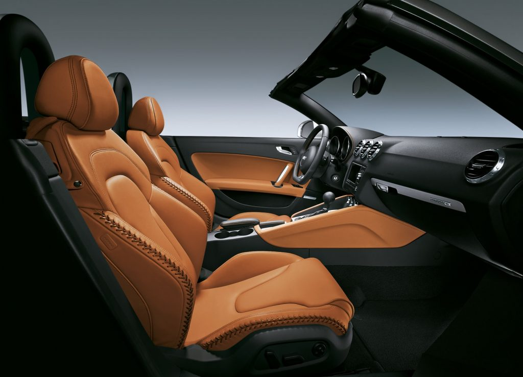 The tan-leather-with-baseball-stitching interior of a 2008 Audi TT Roadster 3.2 Quattro