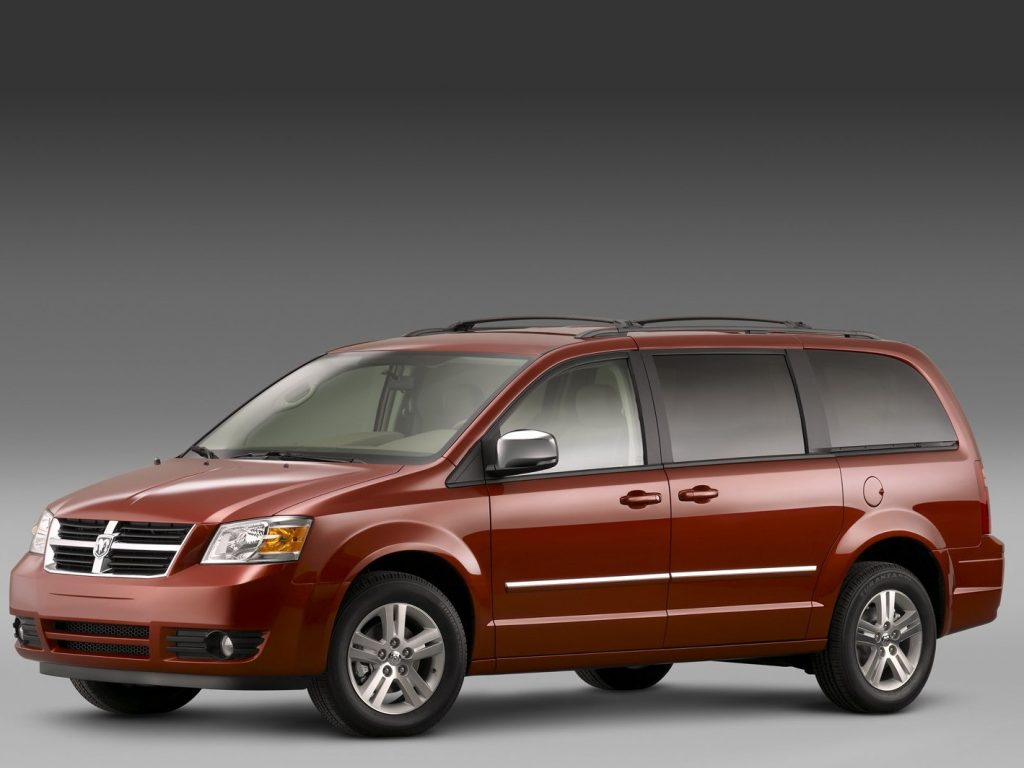 A red 2008 Dodge Grand Caravan minivan against a gray background.