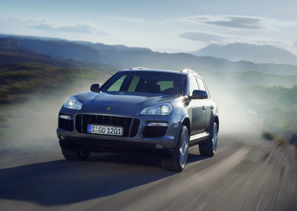 A silver 2008 Porsche Cayenne Turbo driving down a curving desert road, throwing up a plume of dust