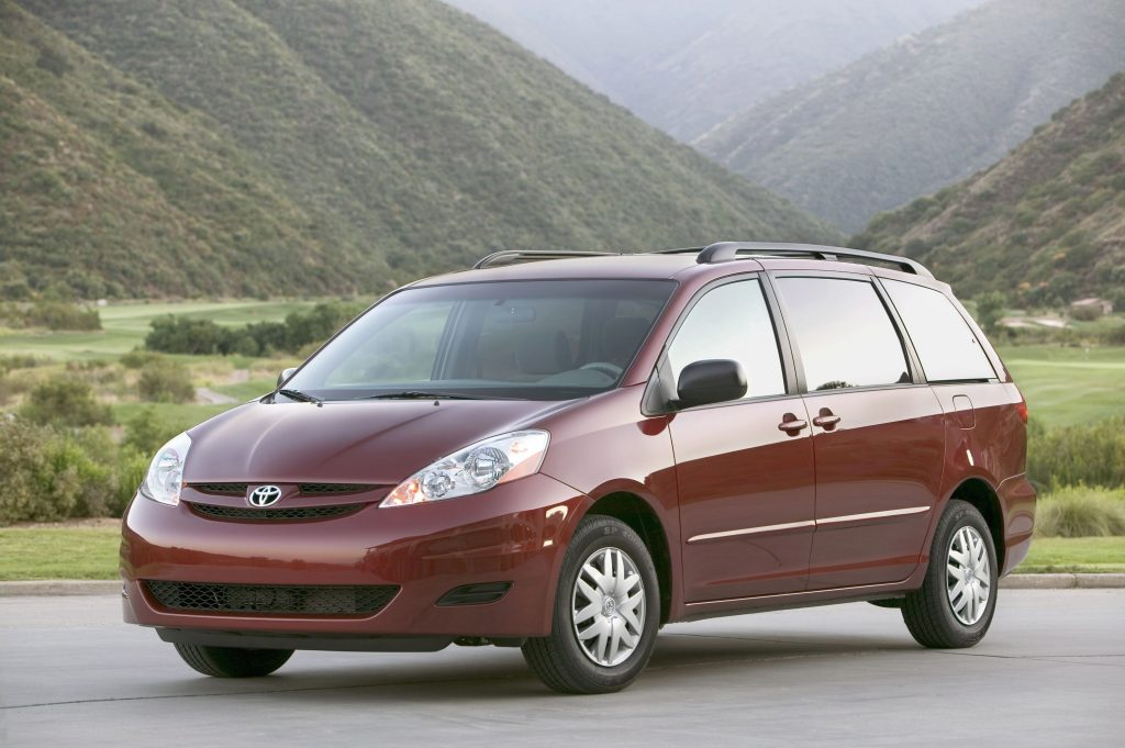 a red older Toyota minivan in a mountain scene