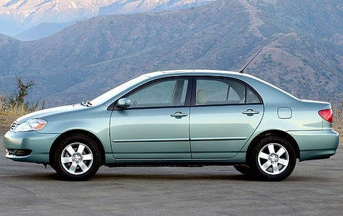 a 2008 Toyota Corolla side view with a mountainous backdrop