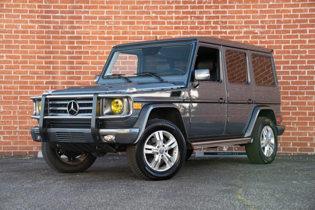 A blue-gray 2009 Mercedes G550 against a red brick wall