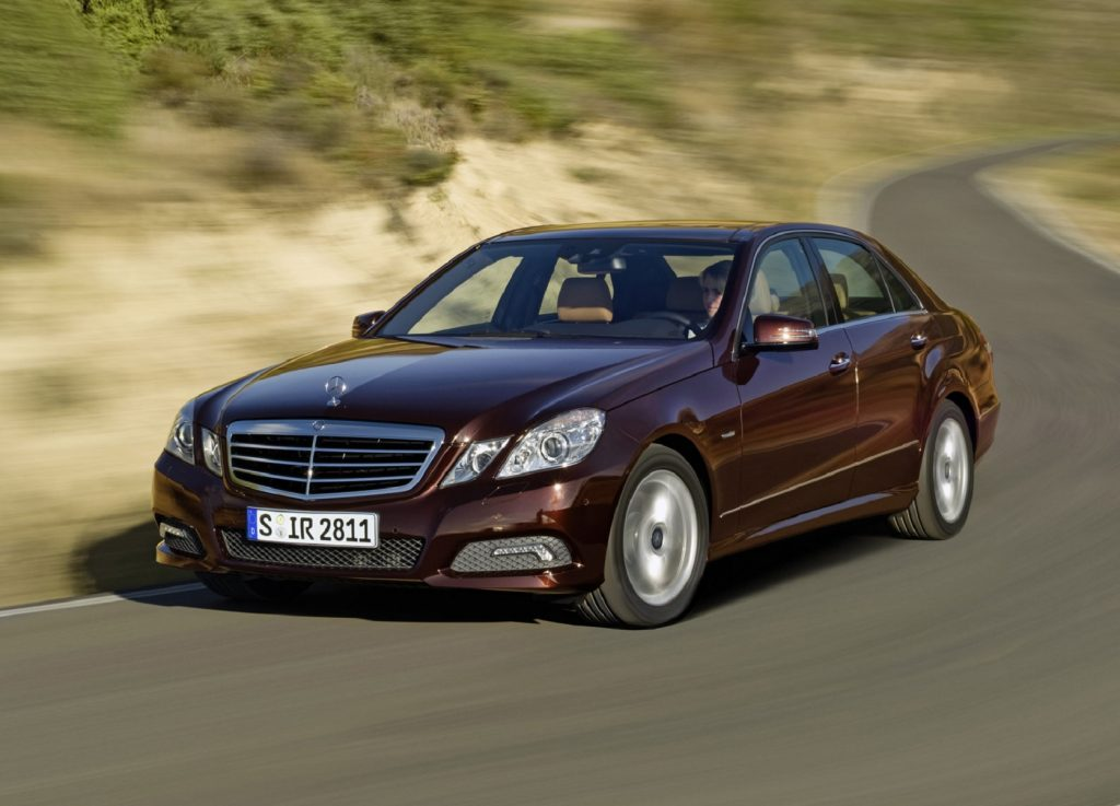 Burgundy-red 2010 Mercedes-Benz E-Class sedan driving down a curving road