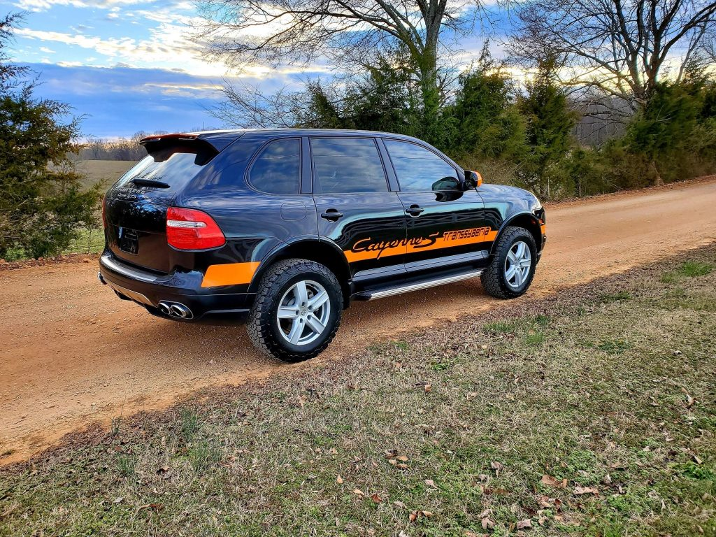 Side-rear view of a black-and-orange-striped 2010 Porsche Cayenne Transsyberia, parked on a gravel forest road