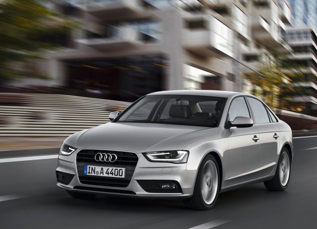 A silver 2013 Audi A4 driving through a city