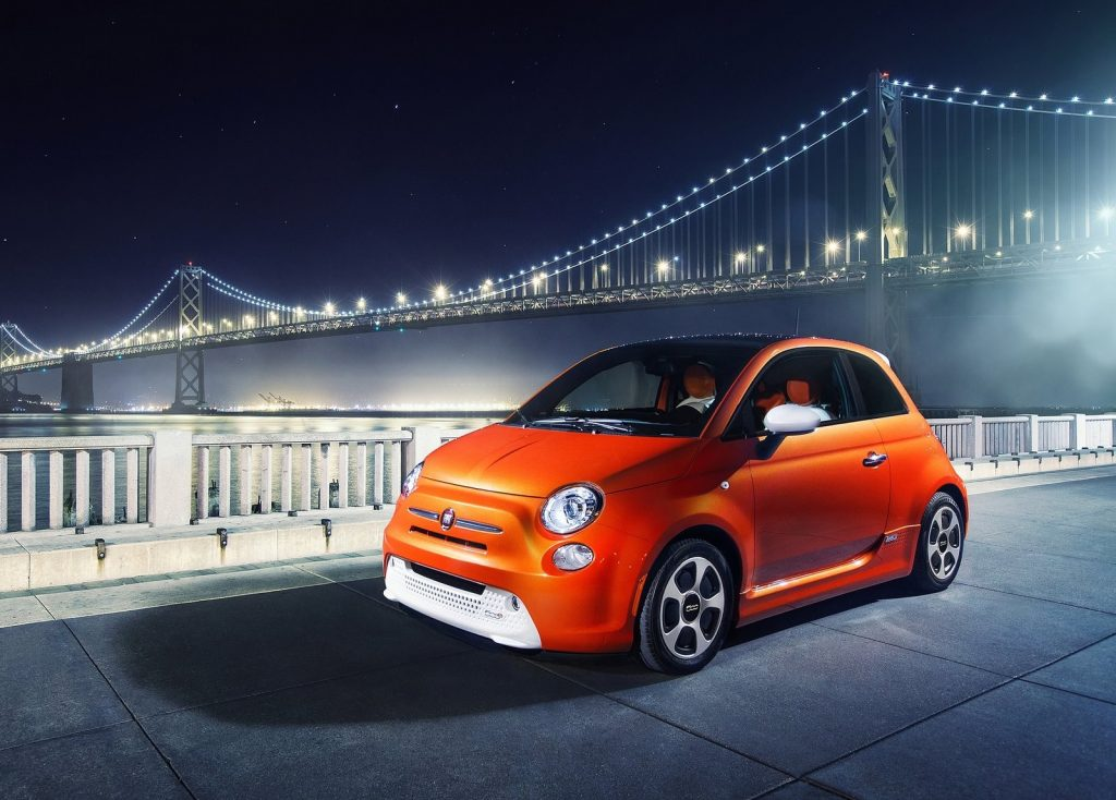 orange Fiat 500e in front of a lit suspension bridge late at night in the city.
